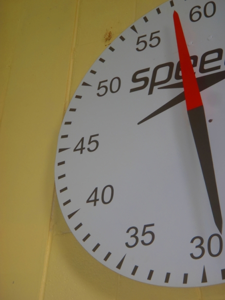 A swimming analogue pace clock, with the single hand almost pointing to 60 at the top.