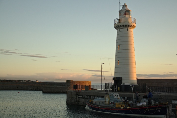 Sunrise hits Donaghadee harbour light, with Quinton Nelsons ex-RNLI boat the Guy and Clare Hunter nestled underneath with the crew onboard