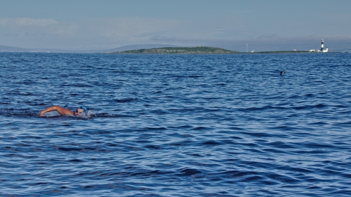 Ninety minutes into swim, with Mew Light house  closer, the errant swim cap attempts to escape
