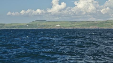 Killantringan lighthouse with wind turbines on the  peaks