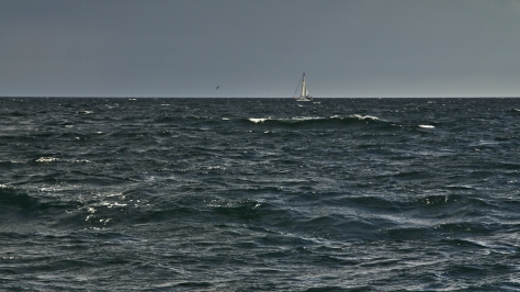 Choppy Force Three water as a yacht sails west