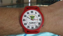 A scarlet large face wristwatch called a Pace Watch with only minute and seconds hands, used for tracking swimmers times and rests