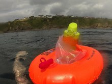 Inflatable swimmer's tow float with sealable cavity