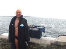 Brother  Loneswimmer wears his personalsed Ice Mile rebel Surf Fur parka before a cold winter swim at the Guillamene.