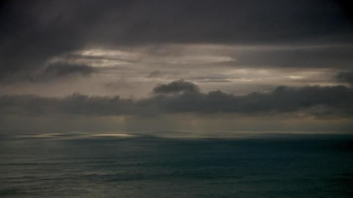 Photot of the Enchlish Channel at dawn, with a cludy sky, and light on the horizon