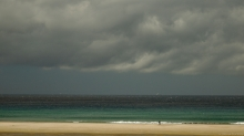A solitary man walks the long low gradient of Spain's Tarifa Beach in an Atlantic onshore breeze