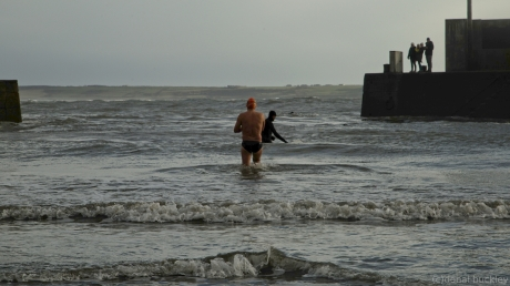 Swimmer in skin and surfer in wetsuit entering water behind Tramore Pier