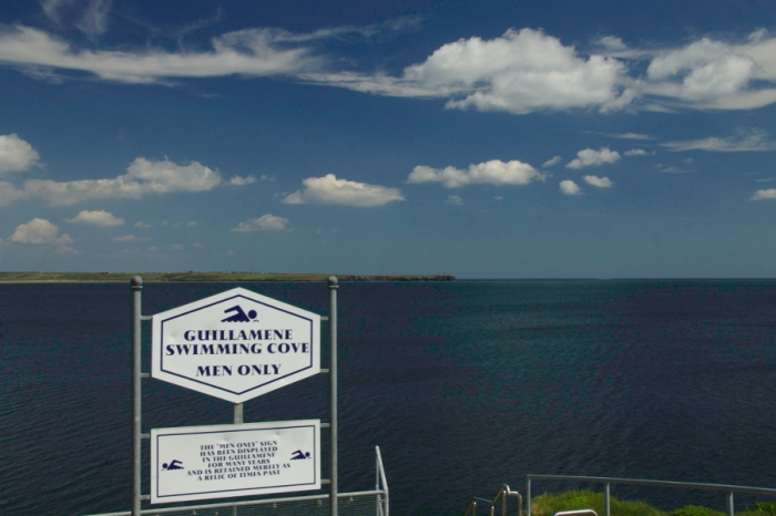 Blue sky with pufffy clouds over Tramoe Bay and the Guillamene swimming club sign